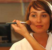 Bride receives a make up application by service provider.