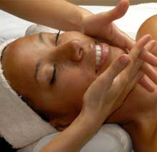 Esthetician massages clients face after treatment while client relaxes atop massage table.