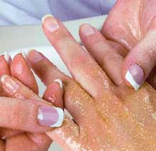 Therapist applies exfoliant to clients hand to help renew skin.