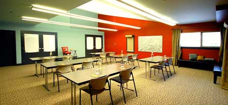 Meeting space with table and chairs set in class room style, and a keynote podium. Walls are painter red with roller paper and space to collaborate ideas.