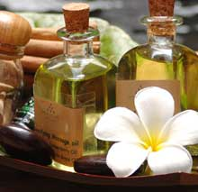 A pair of small jars with massage oils set in a tray with small stones and a white tropical flower in the corner.
