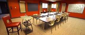 Our smaller meeting room set up with tables and presenter podium. Along walls bulletin boards and roller paper for collaborating ideas.