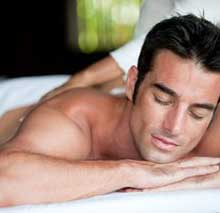 Male client lays atop massage table while esthetician focuses on various skin care needs.