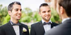 Wedding of two LGBT men, both in black tuxedo jackets and white dress shirts, with officiant.