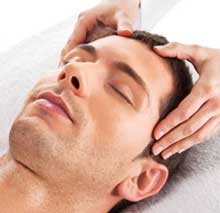 Male client  lays atop a white lines draped massage table while esthetician give a 30 minute facial.