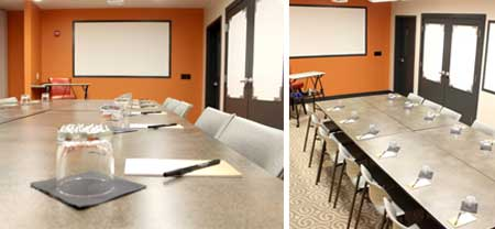 Meeting space with table and chairs set in class room style, and a keynote podium. Walls with roller paper and space to collaborate ideas.