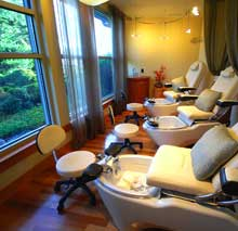 A look into our manicure and pedicure room which has three chairs and views of a tranquil waterfall and pond.