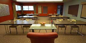 Our meeting room set up  class room style and presenter podium in front. Along the walls are roller paper and bulletin boards for collaborating ideas.