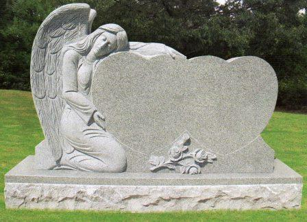 A headstone with an angel next to two hearts