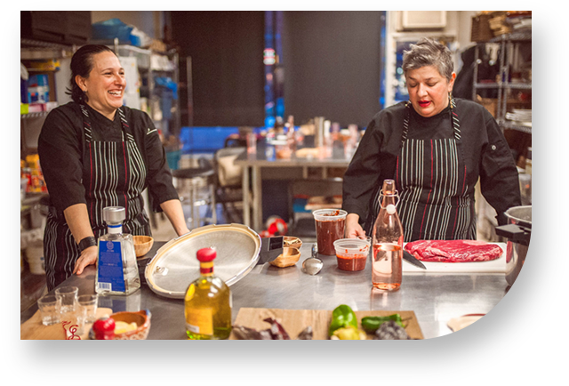 cooking, studio, adriana, pelayo, paola, solorzano, tequila, pepper, red, glasses, chili, kitcken, apron, black, stripes, women, knife, table, green, cutting, board, fridge, beef, steak, water, bottle, mill, table, santo, pecado, mexican, catering, toronto, canada