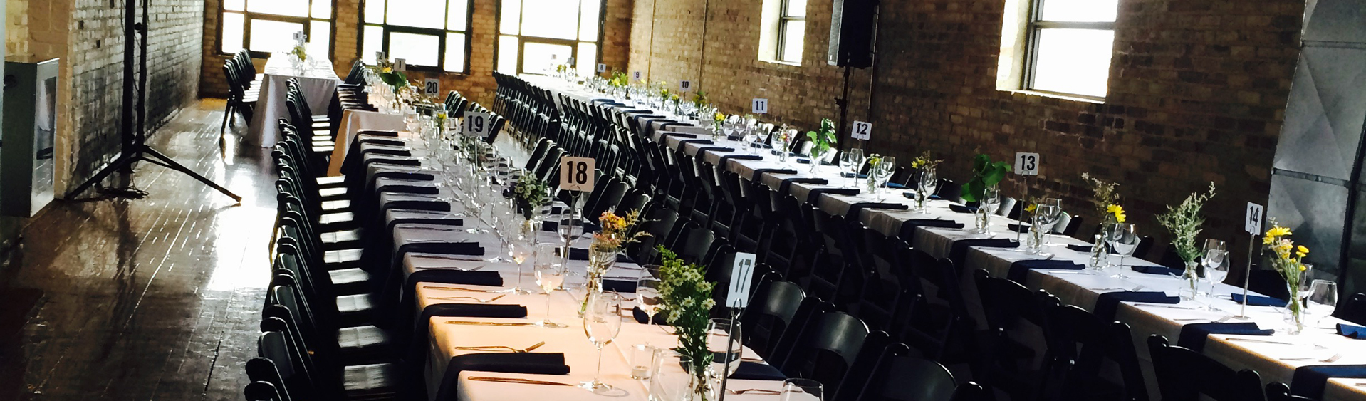 wedding, chairs, black, tables, glass, cups, flowers, table, cloth, napkins, forks, knives, numbers, brick, wall, windows, room, wood, santo, pecado, mexican, catering, toronto, canada
