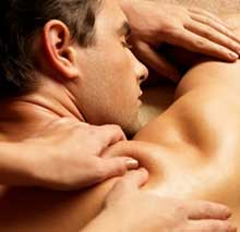 Male client lays on massage table while therapist focuses on the upper right area of his shoulder.