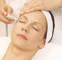 Esthetician applies a targeted treatment to client as she relaxes.