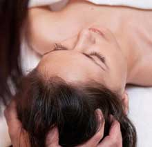 Female client lays atop a massage table while therapist focuses on scalp massage.