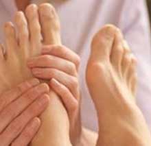 Therapist focuses in on the left foot of client as they apply pressure to alleviate muscle tension in foot and body.