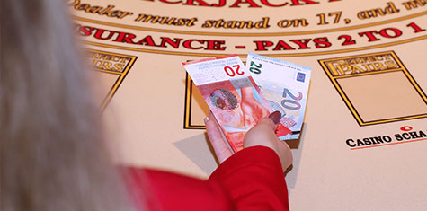 Croupier places two different currencies on the table